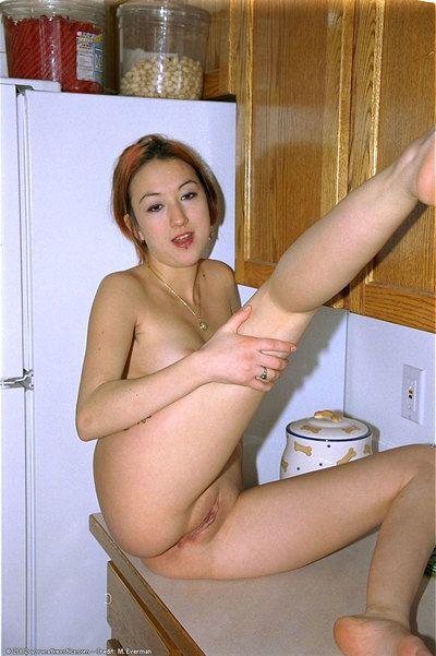 Asian amateur Hazel revealing pierced nipple and bald cunt in kitchen