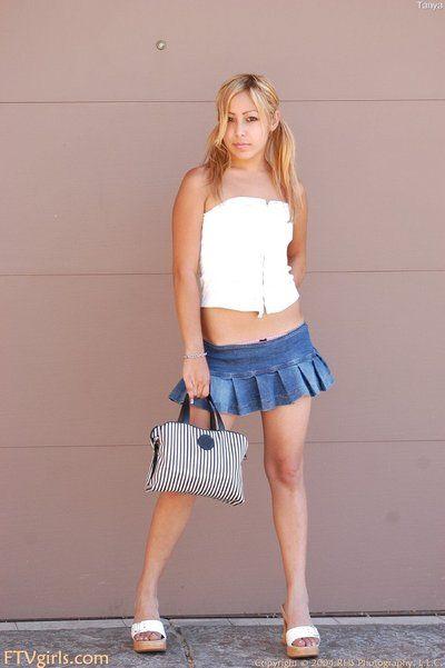 Petite pantyless girl Kat Nubiles in tiny blue skirt spreads her buttocks