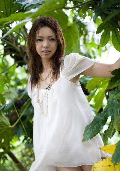Hot and sexy brunette chick from Japan Yura Aikawa is sexily posing outdoors under the tree