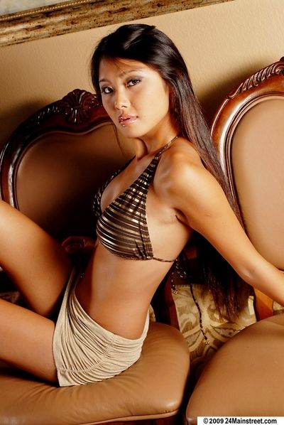 Asian babe Dee takes part in a posing scene, showing off her ass