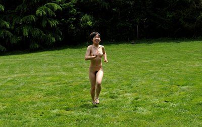 Hot Asian teen babe Youzn Idols is running on the grass glade all nude and showing her hairy pussy
