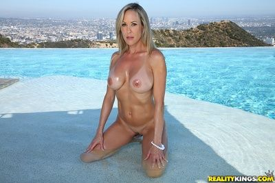 Breasty babe Brandi Keen to shows her milf apple bottoms in strings in outdoor pool