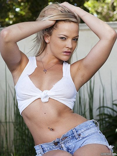 Curvy blonde Alexis Texas poses in shorts, top and boots in the backyard