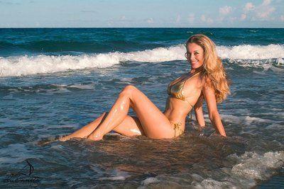 Sexy bodied leggy model Anita Dark in bikini poses on the beach by the sea
