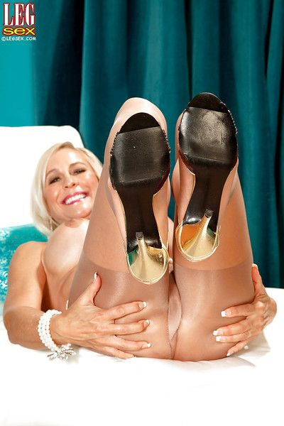 Mature blonde woman Carrie Romano freeing hose clad feet from high heels