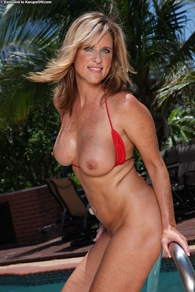 Sexy blonde MILF Jodi West releasing nice natural tits from bikini in pool