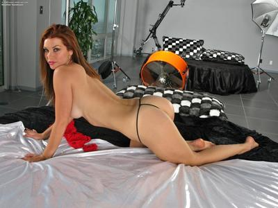 Adorable Heather Vandeven poses with red dildo in her bald pussy and uses speculum on a bed