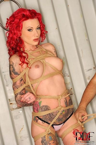 Tattooed redhead fetish model Becky Holt suspended by rope for BDSM shoot