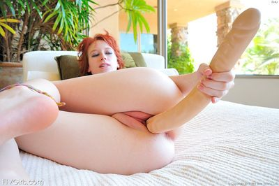 Redhead uses a huge toy cock to please her naughty porn desires