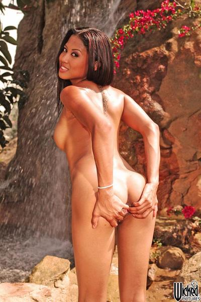 The lusty Asian chick Lily Thai stretches ass cheeks and pussy lips outdoor