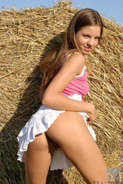 Skinny teen dear Belinda Nubiles takes her clothes off her garments by the haystack and shows her tiny tits.