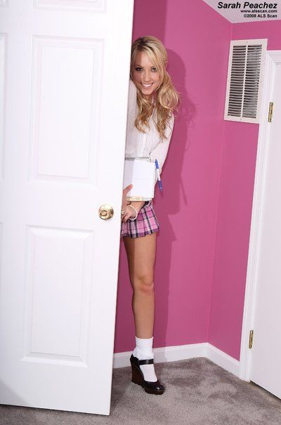 Smiling blonde Sarah Peachez in plaid compact skirt playfully shows her wet crack