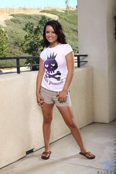 Raunchy exotic lass Bliss Lei removes her white t-shirt, beige shorts and blue shorts