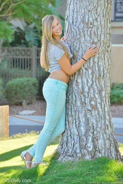 Fully clothed sweetie pulls down jeans on lawn before masturbating inside