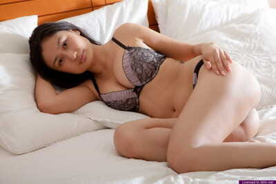 Young Asian amateur doffs her lace underclothes to stretch pussy for closeup