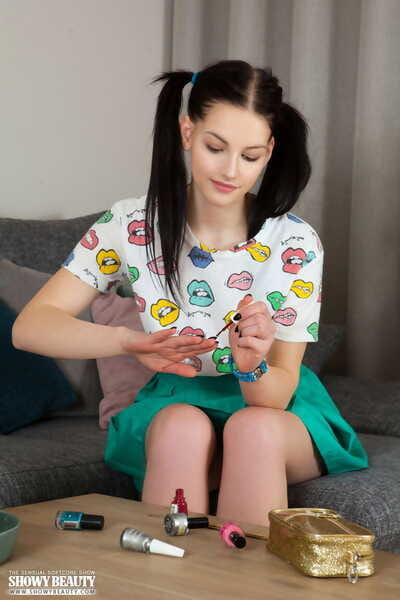 Cute amateur Vienna does her nails prior to modelling completely naked on a sofa