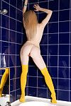 Leggy girl Polly B in yellow stockings exposes her shaved muff all over the bathroom