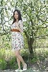 The beautiful Eastern cutie Li Moon is underneath the blossoming tree showing off moist unclothed charms