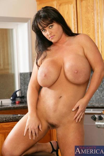 Tanned milf with uncontrolled boobs Indianna Jaymes gets the waters drilled regarding the kitchen